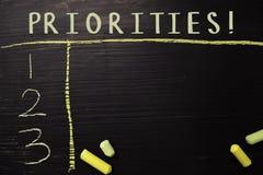 Prioriteter! skriftligt med färgkrita Stöttat av extra service Svart tavlabegrepp arkivfoton