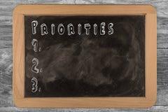 Prioriteter - svart tavla med 3D skisserad text - på trä Royaltyfria Bilder