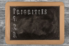 Priorities -  chalkboard with 3D outlined text - on wood. Priorities - chalkboard with 3D outlined text - on wood Royalty Free Stock Images
