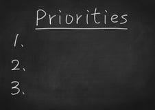 Priorities. Priority concept text on blackboard background Stock Photos