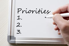 Priorities written on whiteboard. Human hand writing priorities on whiteboard Stock Image