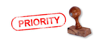 PRIORITY Rubber Stamp. Top view of a rubber stamp with a giant word PRIORITY printed, isolated on white background Stock Photos