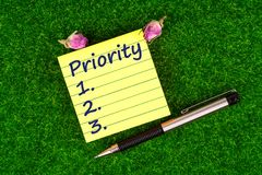 Priority in note. Priority in sticky note with pen and dried rose buds on grass royalty free stock images