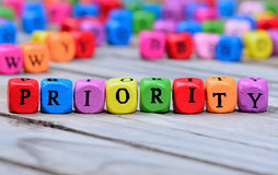 Priority word on wooden table Royalty Free Stock Images