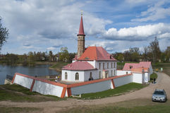 Priory Palace in Gatchina. Russia. Built king Paul 1. White walls, red roof, spire. Blue sky Royalty Free Stock Photography