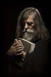 Prière supérieure, vieil homme priant avec des mains sur le livre de bible, au-dessus du Bl Photos stock
