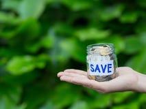 Prise abstraite de main d'économie d'argent un pot en verre images stock