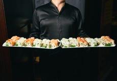 Prise asiatique de cuisinier un plat de petit pain de sushi images stock