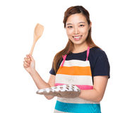 Prise asiatique de femme au foyer avec les gants en bois de poche et de four Photos stock