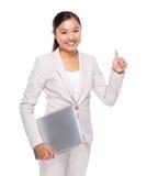 Prise asiatique de femme d'affaires avec l'ordinateur portable et le pouce  Photographie stock libre de droits