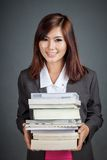 Prise asiatique de fille d'affaires beaucoup de livres et sourire Image stock