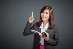 Prise asiatique de fille d'affaires par livre et point  Photographie stock libre de droits