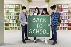 Prise d'étudiants de nouveau au texte d'école dans la bibliothèque Images stock