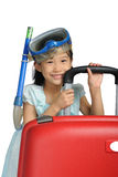 Prise d'air de port et masque de petite fille asiatique près d'un grand rouge de voyage Image libre de droits