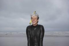 Prise d'air et masque de port d'homme regardant loin sur la plage Images stock