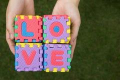 Prise d'amour de mots de puzzle en main avec le fond vert Image libre de droits