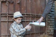 Prise d'enfant par verre de lait frais Photos stock