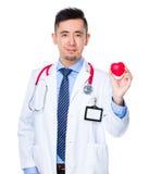 Prise d'homme de docteur avec la boule de coeur Photos stock
