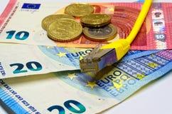 Prise de connexion réseau et billets de banque et pièces de monnaie jaunes d'euro comme fond Image stock