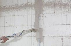Prise de constructeur dans la machine screeding de plâtre de mur automatique de ciment de mains Plâtrage du mur avec le jet plâtr photos libres de droits
