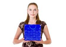 Prise de femme sur le sac bleu de paumes avec le cadeau Image libre de droits