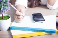 Prise de femme un stylo sur des documents Images stock