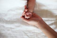 Prise de la main du bébé par le plan rapproché de main de mère Images libres de droits
