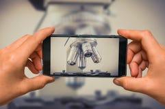 Prise de la photo du microscope biologique avec le téléphone portable photo libre de droits