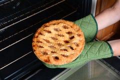 Prise de la tarte aux pommes du four Image libre de droits