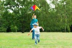 Prise de Launching The Kite de père par son fils photographie stock libre de droits