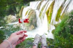 Prise de main de femmes le texte d'amour sur un bâton au-dessus de la cascade Fin vers le haut Photo libre de droits
