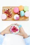 Prise de main de fille par tasse bleue de cappuccino de matin Macarons et pétales de roses français sur le bureau en bois Image libre de droits