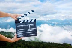 Prise de main une ardoise de film avec la montagne et le ciel images libres de droits
