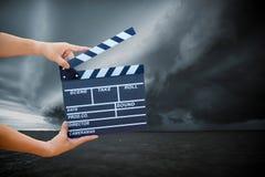 prise de main une ardoise de film avec le nuage de tempête photo stock