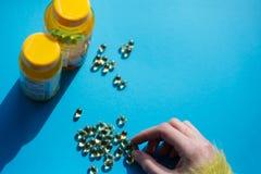 Prise des pilules de médecine de vitamine au-dessus de fond bleu photo stock