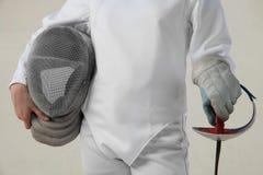 Prise femelle d'escrimeur le masque d'épée et de rencer d'isolement sur le fond blanc Photo stock