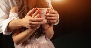 Prise méconnaissable d'homme et de femme avec deux mains une tasse de café chaud Couples dans l'amour Concept de soin d'amour photographie stock