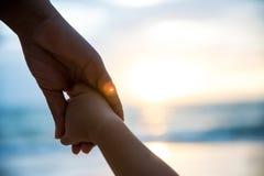 Prise molle de parent de foyer la main de petit enfant pendant le coucher du soleil images stock