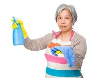 Prise pluse âgé de femme au foyer avec le jet et le chiffon de bouteille Photo stock