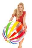 Prise rouge de ballon de plage de robe de femme dans l'avant images stock