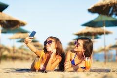 Prise sexy de deux filles selfy sur une plage Photographie stock