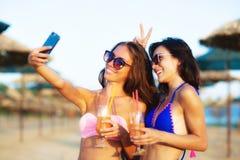 Prise sexy de deux filles selfy sur une plage Images stock