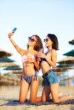 Prise sexy de deux filles selfy sur une plage Image libre de droits