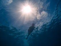 Prises d'air de jeune femme dans l'eau bleue claire Photo de dessous photographie stock
