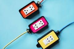 Prises d'alimentation d'énergie d'électricités sur le fond bleu photo stock