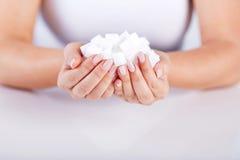 Prises de femme dans des mains des cubes en sucre photographie stock