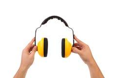 Prises de mains fonctionnant les écouteurs protecteurs. Photos stock