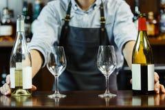 Prises masculines de sommeliers blanches et vin rouge photographie stock