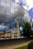 Prishtina mosque reflexion. The famous Prishtina old mosque known as the Carshi Mosque reflected in the windows modern building Stock Photo