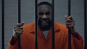 Prisioneiro afro-americano ansioso que guarda barras e que ameaça à câmera, criminoso vídeos de arquivo